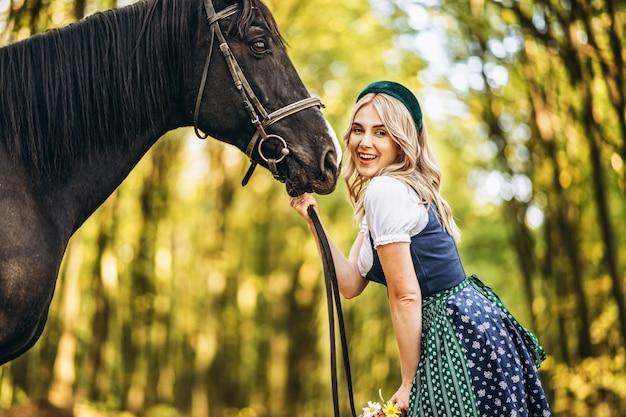 Bionda graziosa in vestito tradizionale che cammina con il grande cavallo nero nella foresta