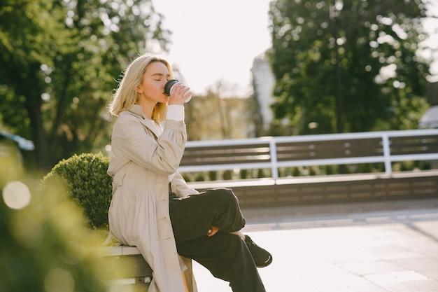 Bionda in una città estiva con una tazza di caffè
