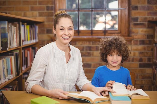 Bionda insegnante e allievo lettura libri in biblioteca