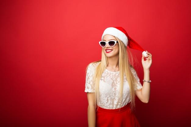 Bionda pensierosa in cappello santa su uno sfondo rosso isolato. occhiali da sole cerchiati bianchi.