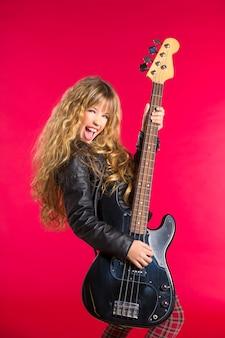 Bionda ragazza rock and roll con basso elettrico su rosso