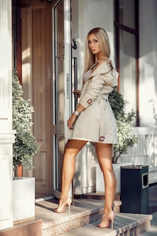 Bionda sexy in lingerie beige e cappotto in posa vicino al caffè. resto e divertimento.
