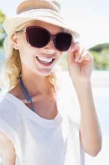 Bionda sorridente con cappello e occhiali da sole guardando la telecamera