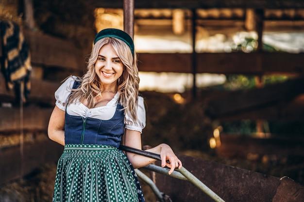 Bionda sorridente graziosa in vestito tradizionale con la carriola che lavora nel cortile.