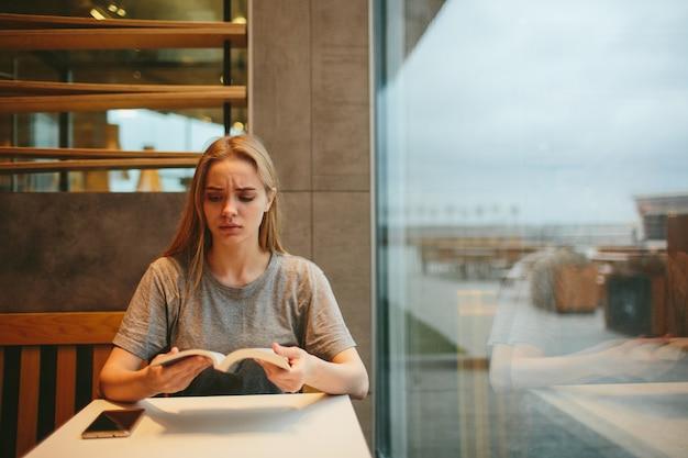 Bionda sta leggendo un libro e sta parlando al telefono in una tavola calda o in un ristorante