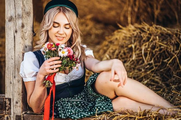 Bionda sveglia in dirndl, vestito tradizionale da festival con il mazzo dei fiori del campo che si siedono sul recinto di legno all'azienda agricola