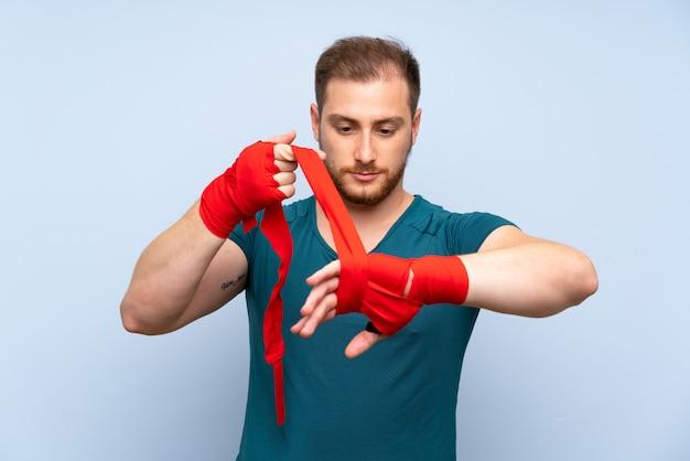 Biondo sportivo uomo in bende di boxe