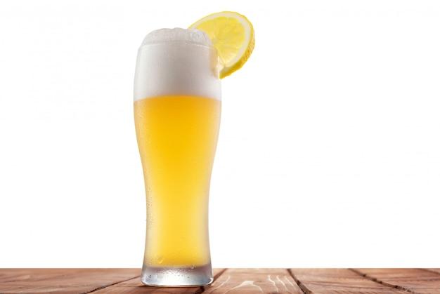 Birra bianca con limone su uno sfondo isolato