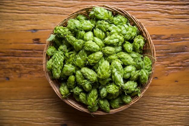 Birra che fa gli ingredienti coni di luppolo in orecchie di legno della ciotola e del grano su fondo di legno. concetto di birrificio di birra.