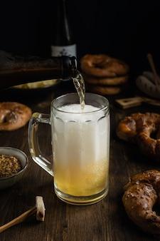 Birra che versa in vetro con le ciambelline salate, il bratwurst e gli spuntini sulla tavola di legno rustica