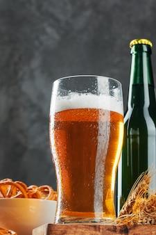Birra chiara e snack sul tavolo di pietra. cracker, patatine vista laterale