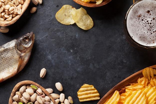 Birra chiara e snack sul tavolo di pietra