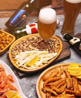 Birra chiara e spuntini sul tavolo di legno. noci, scaglie di formaggio, pistacchi, creme