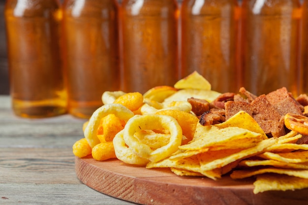 Birra chiara e spuntini sulla tavola di legno. noci, patatine, pretzel