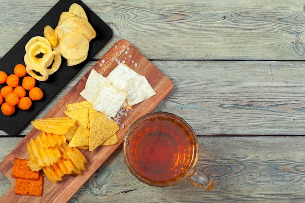 Birra chiara e spuntini sulla tavola di legno.