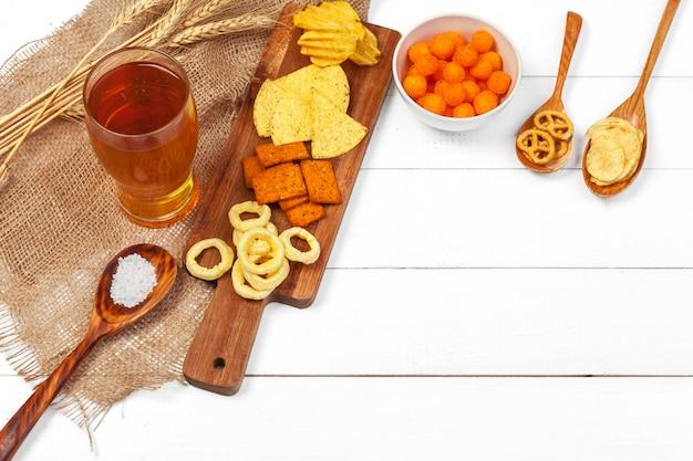 Birra chiara e spuntini sulla tavola di legno