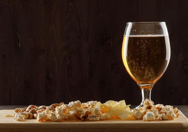 Birra con spuntino in un bicchiere calice sul tavolo di legno e tagliere, vista laterale.