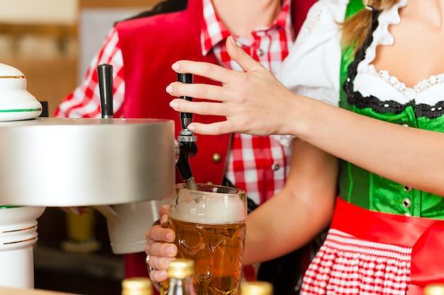 Birra del disegno della giovane donna in ristorante o in pub