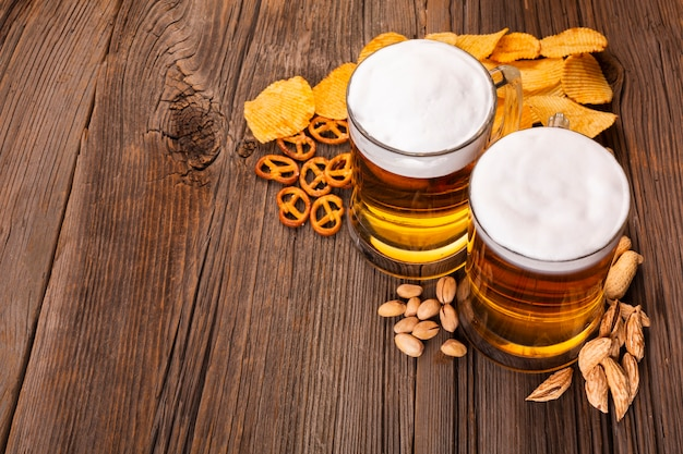 Birra del primo piano con gli spuntini sulla tavola di legno