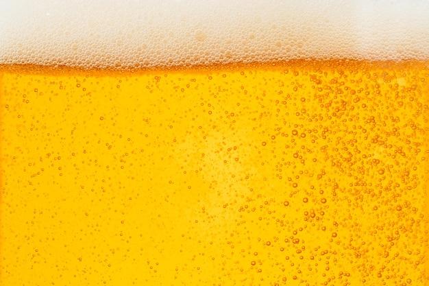 Birra di versamento con schiuma di bolle in vetro per lo sfondo