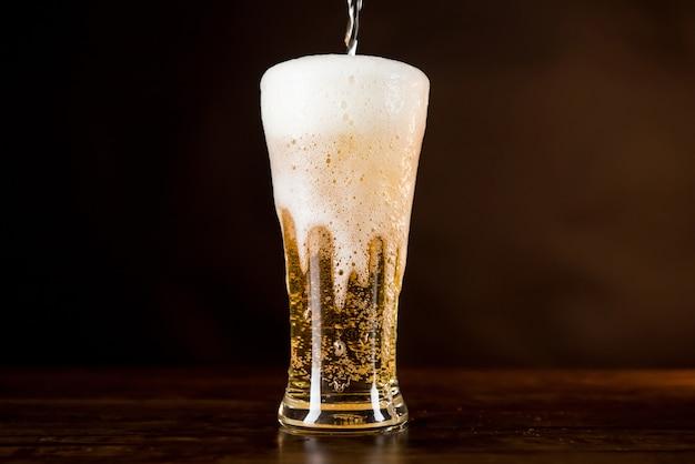 Birra fredda dorata che viene versata nel bicchiere con schiuma schiumosa traboccante