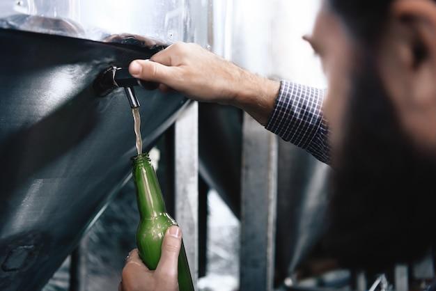 Birra fresca di versamento nella pianta della fabbrica di birra della bottiglia