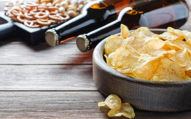 Birra in bottiglie di vetro e snack salati per la birra. fondo in legno marrone. concetto di una festa per gli amici.