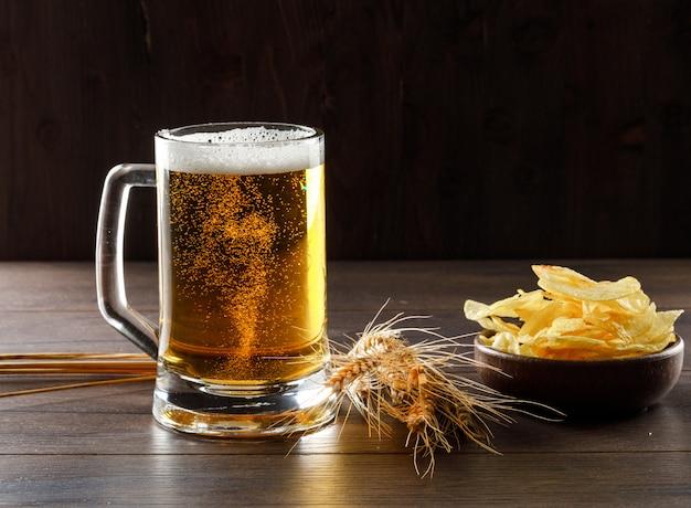 Birra in un bicchiere con spighe di grano, patatine fritte vista laterale su un tavolo di legno