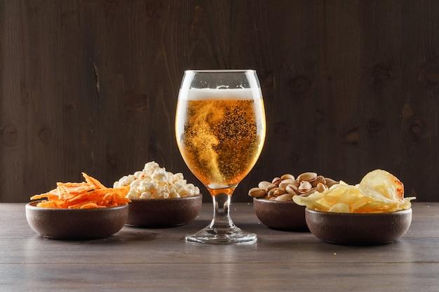 Birra in un bicchiere di calice con vista laterale di cibo spazzatura su un tavolo di legno