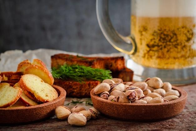 Birra in un bicchiere, pistacchi, crostini e cracker di segale su un tavolo di legno