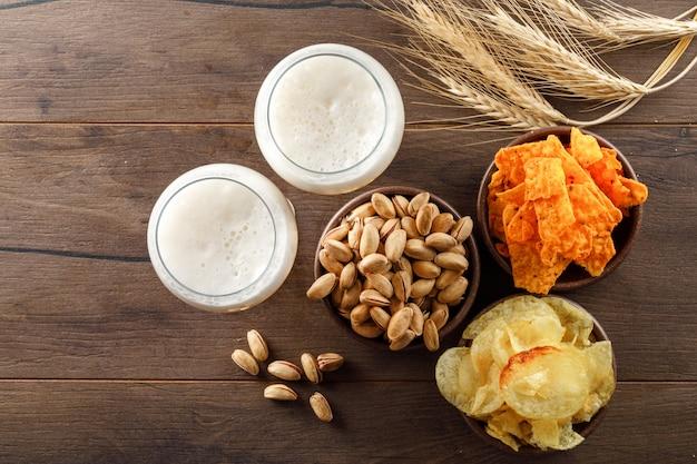 Birra schiumata in bicchieri con pistacchio, spighe di grano, patatine vista dall'alto su un tavolo di legno