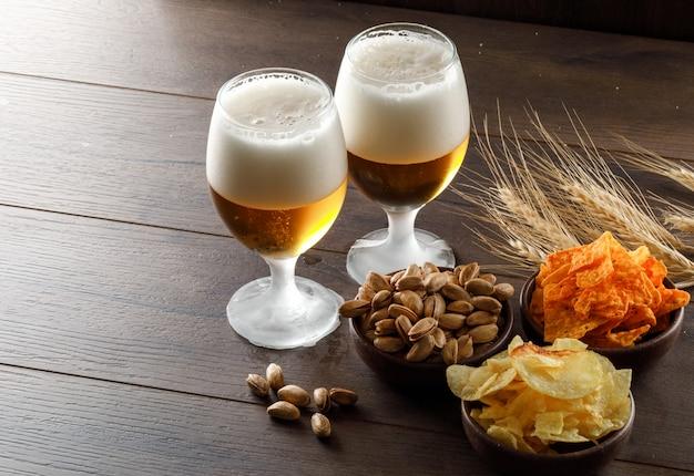 Birra schiumata in calici con pistacchio, spighe di grano, patatine fritte vista dall'alto su un tavolo di legno