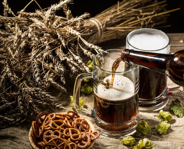 Birra schiumosa dalla bottiglia versata nella tazza in piedi con birra piena di boccali di frumento e luppolo, cesto di pretzel