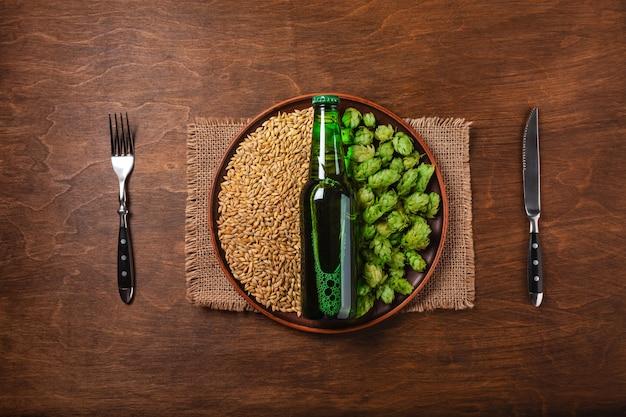 Birra su un grano verde fresco e grano con coltello e forchetta in un piatto contro il bordo marrone in legno