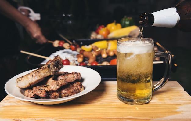 Birra versando con griglia di maiale barbecue