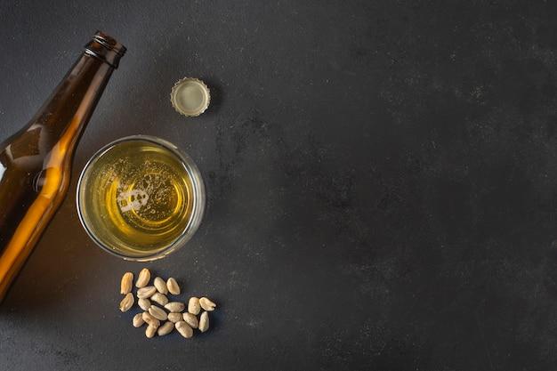 Birra vista dall'alto su vetro e bottiglie con arachidi accanto
