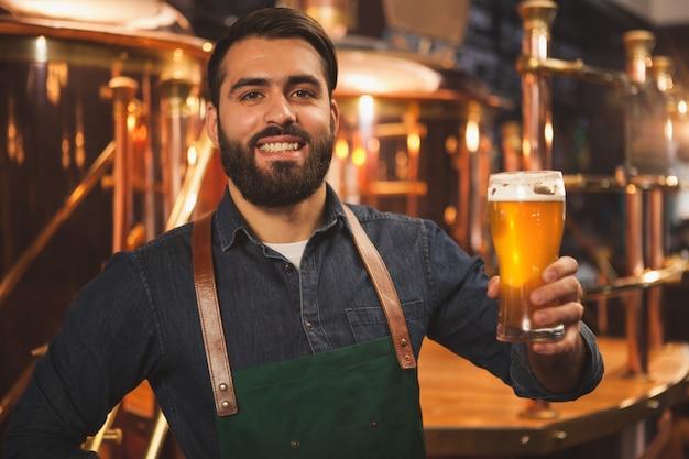 Birraio allegro che gode lavorando nel suo birrificio