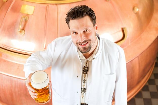 Birraio con bicchiere di birra nel birrificio