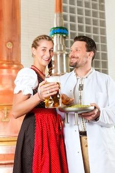 Birraio e donna con un bicchiere di birra nel birrificio