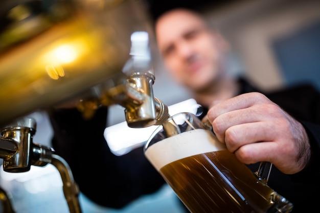 Birraio riempiendo la birra nel bicchiere da birra dalla pompa della birra