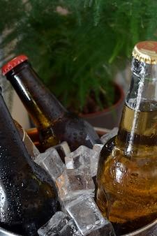 Birre diverse su un tavolo di legno. ci sono bottiglia e bicchiere con ghiaccio per tenerli al freddo