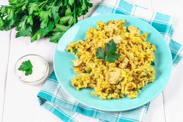 Biryani indiano con pollo, yogurt e spezie in un piatto sulla tavola di legno. capodanno, piatto natalizio