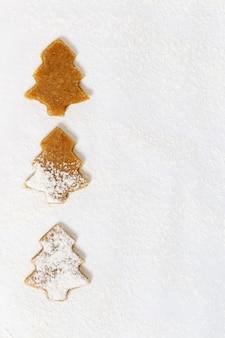 Biscotti a forma di albero di natale su carta per la cottura.