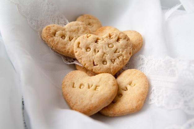 Biscotti a forma di cuore con amore. san valentino da forno a forma di cuore su una superficie di chiffon bianco