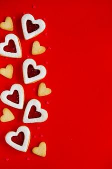Biscotti a forma di cuore con marmellata e zucchero a velo su una tavola rossa