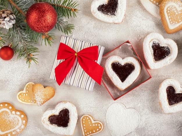 Biscotti a forma di cuore fatti in casa con marmellata di lamponi sulla tavola di legno bianco per natale o san valentino. vista dall'alto.