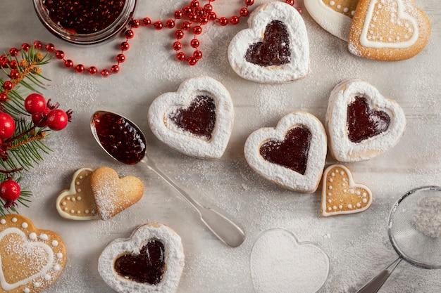Biscotti a forma di cuore fatti in casa con marmellata di lamponi sulla tavola di legno bianco per natale o san valentino.