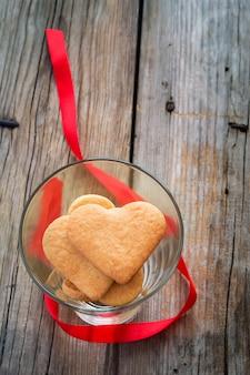 Biscotti a forma di cuore in un bicchiere. san valentino sfondo