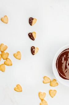 Biscotti a forma di cuore per san valentino ricoperti di cioccolato su marmo chiaro