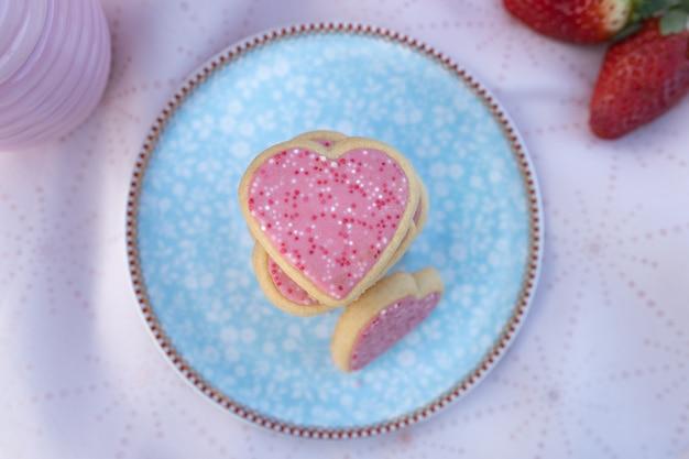 Biscotti a forma di cuore rosa sul piatto decorato